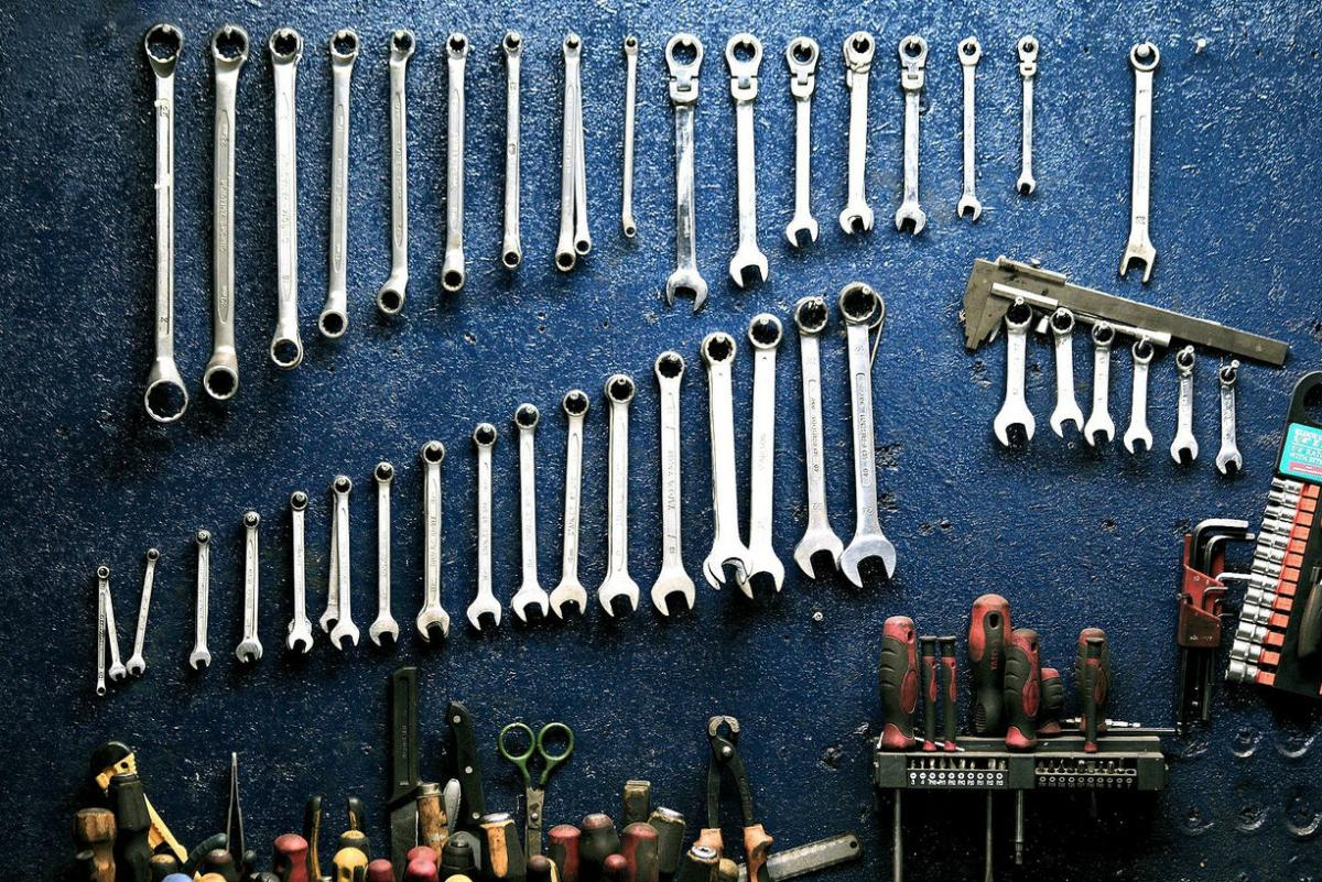 A set of spanners/wrenches hung on a blue wall